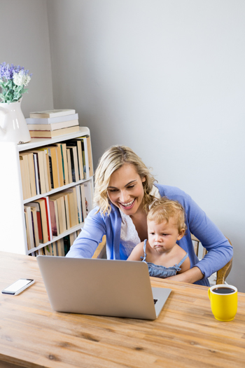 Mother and baby sitting at table and using laptop